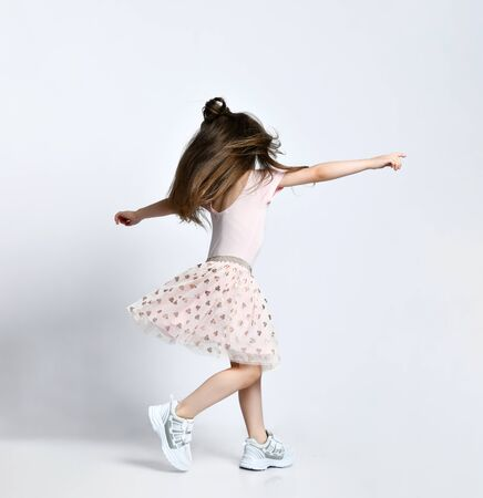 Small girl in casual summer dress and white sneakers standing backwards and moving over white wall background in photo studio. Stylish children clothing concept