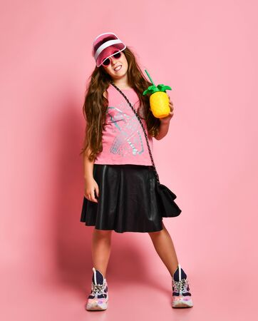 Young happy plus size girl model in stylish summer casual clothing, accessories, sneakers standing and holding healthy diet cocktail in hand over pink background. Weight loss and balanced food concept 写真素材