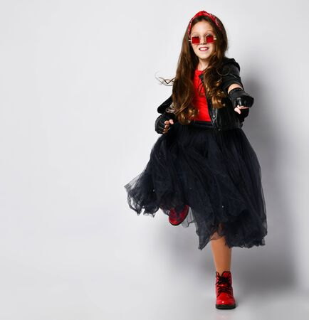 Young positive plus size girl model in bright rock style clothing, red boots and square glasses dancing over white background. Trendy youth casual fashion concept
