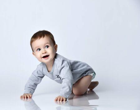 Niño pequeño bebé en mono casual gris y descalzo arrastrándose por el suelo, sonriendo y mirando hacia arriba sobre la pared blanca de fondo. Ropa de bebé de moda, primeros pasos y concepto de infancia feliz
