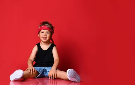 Adorable boy in stylish casual clothing, hair bandana and white sneakers sitting on floor and smiling over red background. Trendy children clothing, happy childhood concept Stockfoto
