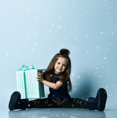 Small smiling girl in t-shirt, leather leggins and ugg boots sitting on floor and holding big present box over blue snowflake wall background. Stylish children clothing and winter holidays concept