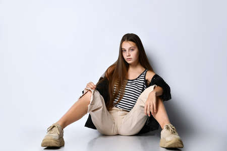 Teenage female with long hair, in striped t-shirt, black denim jacket, beige pants and sneakers. She is sitting on the floor isolated on white. Sincere emotions, hipster style. Copy space. Close up