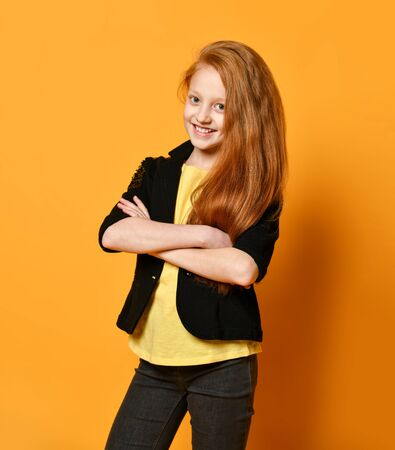 Red-haired teenage girl in black jacket and pants, yellow t-shirt. She is smiling, hands folded, posing against orange studio background. Sincere emotions, fashion, beauty. Close up, copy space Stockfoto