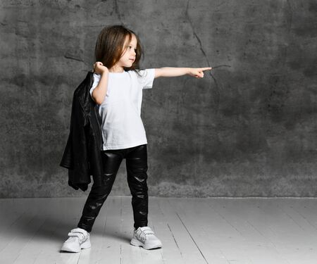 Small girl in black and white rock star style casual clothing and white sneakers standing and pointing aside with finger over grey concrete background in studio. Stylish children clothing concept Stockfoto