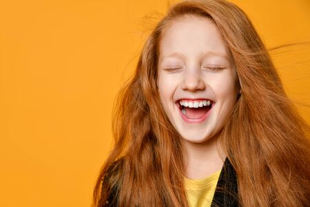 Red-headed teenage child in black jacket and yellow t-shirt. She is laughing with closed eyes, posing against orange studio background. Sincere emotions, fashion, beauty. Close up, copy space