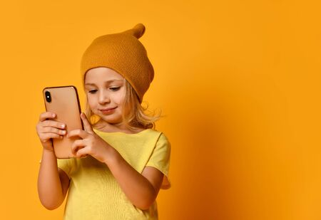 Little blonde kid dressed in t-shirt and hat, holding smartphone, watching videos, looking at screen with joyful smile, posing on yellow studio background. Technology, children, internet. Close-up