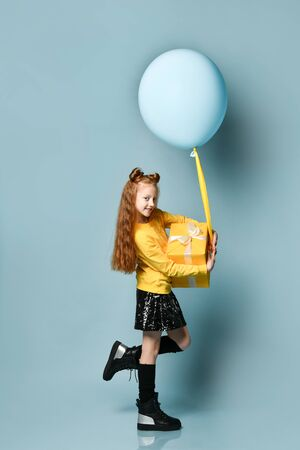 Red-headed teen child in yellow sweatshirt, black skirt, knee-highs, boots. Smiling, holding balloon and golden gift box, posing sideways on blue background. Hipster, fashion, holiday. Full length Stockfoto