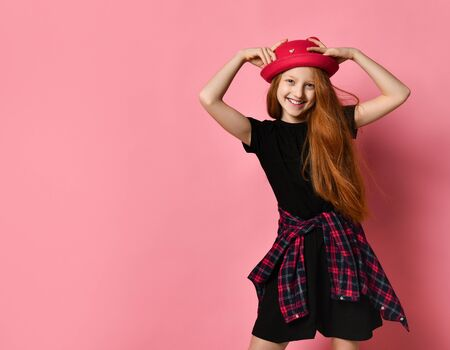 Red-headed teenage kid in black dress, checkered shirt on waist. She smiling, touching her red hat, posing against pink studio background. Hipster style, fashion, beauty. Close up, copy space