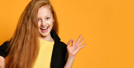 Ginger teenage girl is smiling, showing okay sign by her hand posing on orange studio background. in black jacket and pants, yellow t-shirt. Sincere emotions, fashion, beauty. Close up, copy space Stockfoto