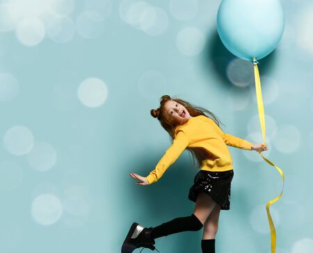 Cheerful red-haired girl teenager with a huge blue inflatable balloon, bounce flying on a blue background with bokeh.