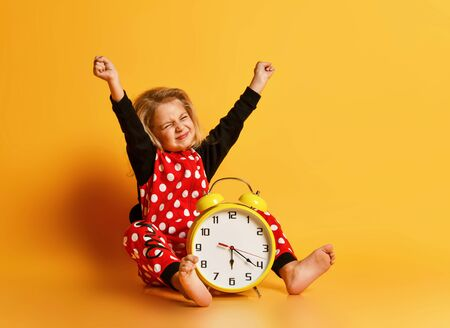Little happy blond girl in red dotted pajamas sitting on floor with big alarm clock and feeling excited with raised hands over yellow background. Different times of day and children schedule concept