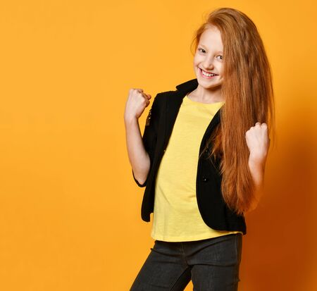 Ginger schoolgirl in black jacket and pants, yellow t-shirt. She is smiling, looking satisfied, posing on orange studio background. Sincere emotions, fashion, beauty. Close up, copy space