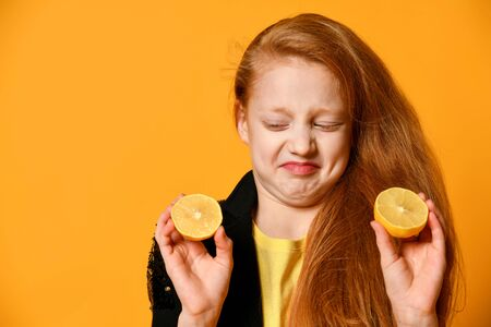 Red-haired teenage kid in black jacket and yellow t-shirt. She making face while looking at halves of lemons in her hands, posing on orange background. Emotions, fashion, beauty. Close up, copy space