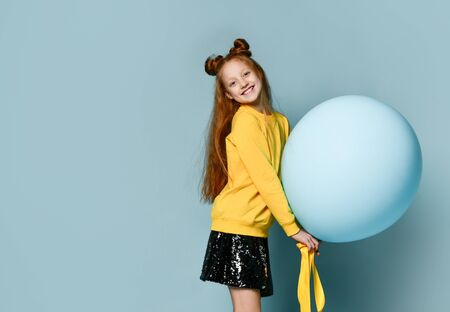 Red-headed teenage girl with fancy hairstyle in yellow sweatshirt, black skirt, . She holding balloon, posing sideways on blue background. Hipster style, fashion, holiday. Stockfoto