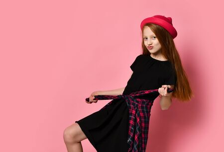 Red-haired teenage girl in black dress and red hat. She tightens checkered shirt on her waist, kissing you, posing against pink studio background. Hipster style, fashion, beauty. Close up, copy space Stockfoto