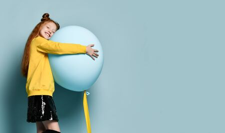 Ginger teenage child with fancy hairstyle, in yellow sweatshirt, black skirt, . Smiling, hugging balloon, posing sideways on blue background. Hipster, fashion, holiday.