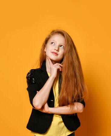 Ginger teenage child in black jacket and pants, yellow t-shirt. She looking thoughtful propping her chin by hand, posing on orange background. Sincere emotions, fashion, beauty. Close up, copy space