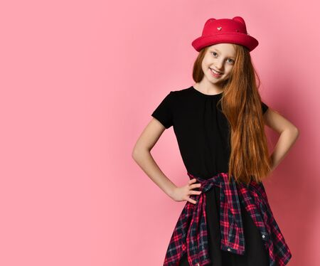 Ginger teen female in black dress, checkered shirt on waist, red hat. She is laughing, hands on hips, posing against pink studio background. Hipster style, fashion, beauty. Close up, copy space