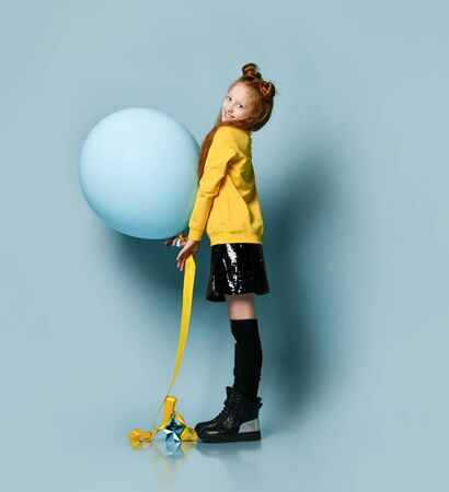 Ginger teenage girl with fancy hairstyle, in yellow sweatshirt, black skirt, knee-highs and boots. She smiling, holding balloon, posing on blue background. Hipster style, fashion, holiday. Full length