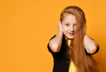 Red-headed teenage kid in black jacket and yellow t-shirt. She closed her ears with hands, posing against orange studio background. Sincere emotions, fashion, beauty. Close up, copy space Stockfoto