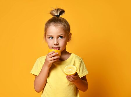 Little cute blond girl in yellow t-shirt holding and licking half of fresh ripe lemon fruit over yellow background. Healthy lifestyle and clean eating concept