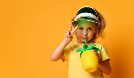 Little smiling cute blond girl in yellow t-shirt and hat drinking fresh healthy fruit juice from straw over yellow background. Healthy lifestyle and clean eating concept Stockfoto