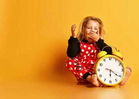 Little blond girl in red dotted home clothing sitting on floor with big yellow alarm clock and yawning over yellow background. Different times of day and children schedule concept Stockfoto