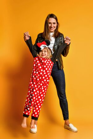 Young happy mother hanging her little smiling blond girl in red dotted pajamas in hands over yellow background. Happy family time together concept Stockfoto