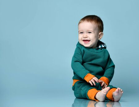 Little baby boy in stylish casual jumpsuit barefoot sitting on floor and smiling over blue wall background. Trendy baby clothing and happy childhood concept