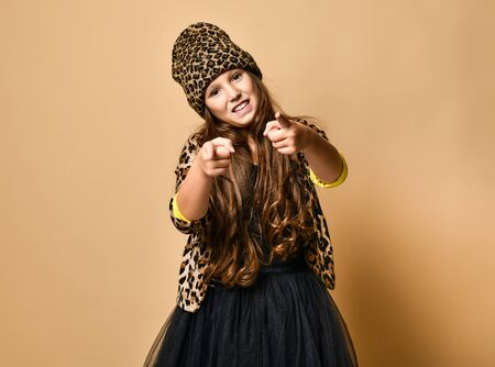 Young plus size girl model in stylish leopard colored casual clothing and black skirt standing and pointing at camera over yellow wall background. Trendy youth fashion concept Stockfoto