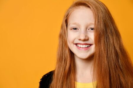 Red-haired teenage kid in black jacket. She is smiling and looking at you, posing against orange studio background. Sincere emotions, fashion, beauty. Close up, copy space