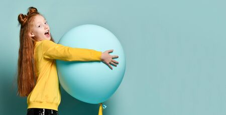 Ginger teenage kid with fancy hairstyle in yellow sweatshirt. Smiling, holding balloon, posing sideways on blue background. Hipster style, fashion, holiday.