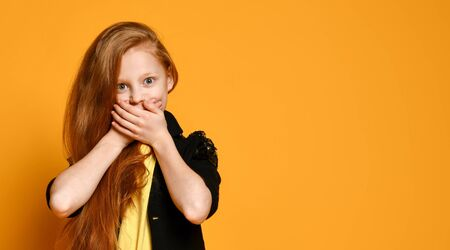 Red-headed teenage girl in black jacket , yellow t-shirt. She is shocked, covered her mouth with palms, posing on orange background. Sincere emotions, fashion, beauty. Close up, copy space