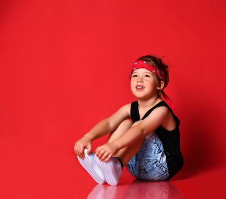 Cute boy in stylish casual clothing, red hair bandana and white sneakers sitting on floor and feeling thoughtful over red background. Trendy children clothing, happy childhood concept