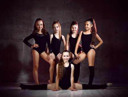 Team of young smiling girls gymnasts in black sport body and uppers posing over grey background. Rhytmhic gimnastics beauty and team sport cocnept
