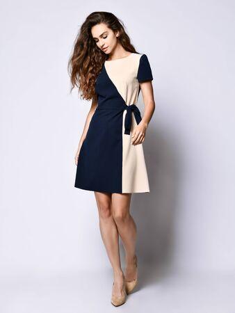 Luksusowa kręcona modelka w dwukolorowej sukience i pełnej długości szpilkach. Śliczna dziewczyna w romantycznych ciuchach idzie na randkę, do biura, na spotkanie.