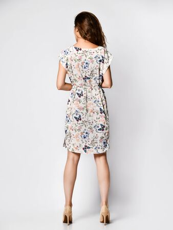 Back view of female model in a silk dress light foot with floral print in full growth. Cute girl in romantic clothes goes on a date, smiling pretty on a white background.