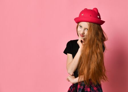 Ginger teenager in black dress, checkered shirt on waist, red hat. She is smiling, touching her face, posing against pink studio background. Hipster style, fashion, beauty. Close up, copy space Stockfoto