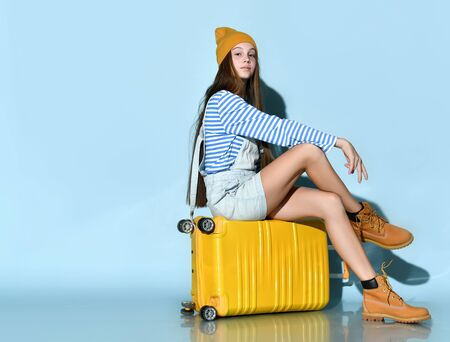 Teenage girl in jeans overall skirt, striped sweatshirt, boots and hat. She smiling, sitting cross-legged on yellow suitcase, blue background. Hipster style, fashion, beauty. Copy space. Full length Stockfoto