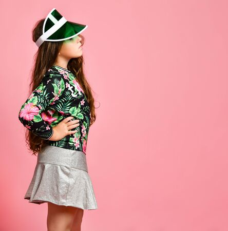 Young plus size girl model in stylish floral printed casual clothing and modern cap standing sideways and looking aside over pink wall background. Trendy youth clothing concept