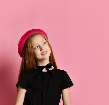 Ginger teenage girl in black dress, checkered shirt on her waist, red hat and choker. She smiling while posing against pink studio background. Hipster style, fashion, beauty. Close up, copy space Stockfoto