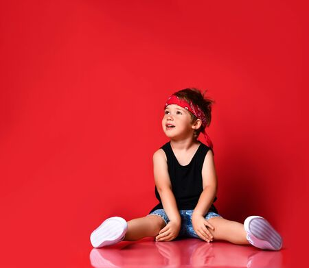 Adorable boy in stylish casual clothing, hair bandana and white sneakers sitting on floor and looking away over red background. Trendy children clothing, happy childhood concept