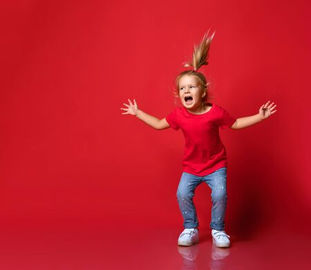 Small happy excited blond girl in stylish casual clothing and white sneakers jumping and feeling playful over red wall background. Trendy children clothing and happy childhood concept