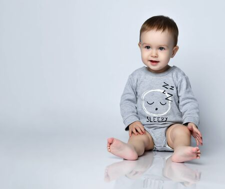Little baby boy toddler in grey casual jumpsuit and barefoot sitting on floor and smiling over white wall background. Trendy baby clothing, first steps and happy childhood concept