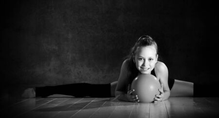 Young smiling girl gymnast in black sport body and uppers sitting in twine on floor and holding pink gymnastic ball in hands over dark background. Rhythmic gymnastics beauty concept Stockfoto