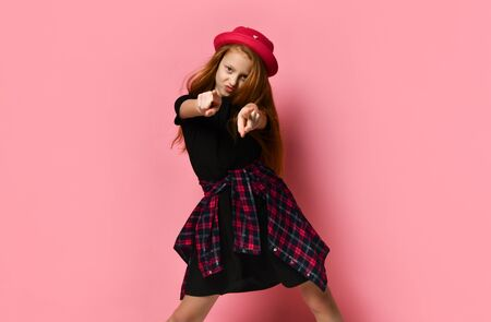 Ginger teenage child in black dress, checkered shirt on her waist, red hat. She pointing at you while posing against pink studio background. Hipster style, fashion, beauty. Close up, copy space Stockfoto