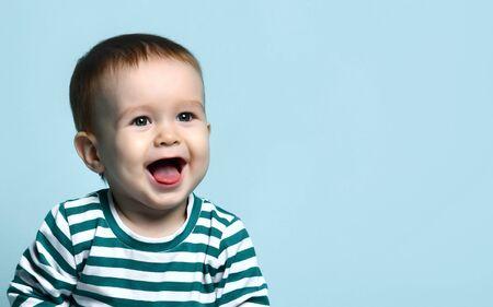Porträt eines süßen Kleinkindes 1 Jahr alt in einer gestreiften Jacke auf blauem Hintergrund, freut sich lachend, nachdem es seine Mutter gesehen hat