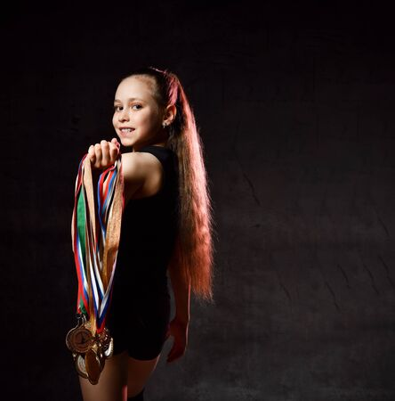Cute girl gymnast in black sport body and uppers walking backwards with many gold medals on shoulder over dark background. Rhytmhic gimnastics beauty, winner, champion, competition cocnept Stockfoto