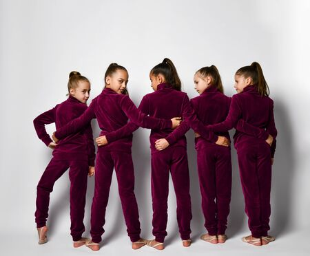 Group of young smiling girls gymnasts in dark red velvet sport costumes standing backwards and embracing each other over white background. Rhytmhic gimnastics beauty and team sport cocnept Stockfoto